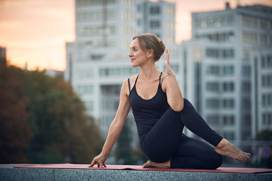 Beautiful young woman practices yoga asana Ardha Matsyendrasana - Half Spinal Twist pose outdoors against the background of a modern city