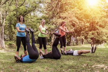 three couples sporting their exercises outdoor together. sportsmen push up their legs to train abdominal muscles similar to situps. Fotomurales