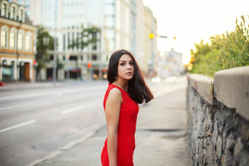 Beautiful Girl in a red dress is standing near of the roadway.