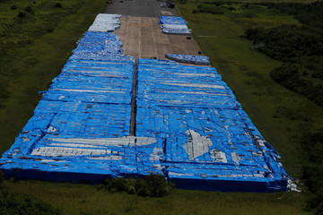 About 20,000 pallets of unused water bottles are seen along an airplane runway a year after Hurricane Maria devastated Puerto Rico in Ceiba