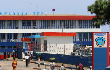 People walk outside the headquarters of the Liberian National Police in Monrovia
