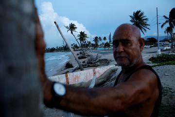 A local resident stands in an area affected by Hurricane Maria, which devastated Puerto Rico last year, in Loiza, Puerto Rico