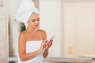 attractive woman using gadget at spa salon