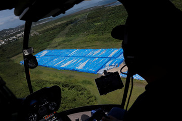 Pallets of unused water bottles are seen along an airplane runway a year after Hurricane Maria devastated Puerto Rico in Ceiba
