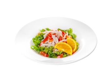 Salad with seafood with squid, tomato, bell pepper, fish, salmon, lettuce and orange, citrus on plate, white isolated background Side view. For the menu, restaurant, bar, cafe