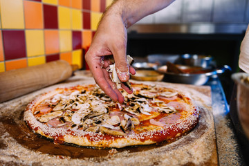 Tuinposter Pizzeria Putting Mushrooms On Pizza In Pizza Restaurant
