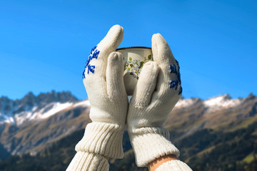 Iron mug with hot tea in female hands in knitted mittens in a winter Alps and forest of national park in Switzerland.