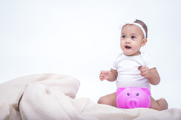 Cute baby saving money in the piggy bank - kid saving money for future concept.