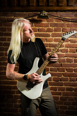 Young man with a blonde hair playing rock music in pub