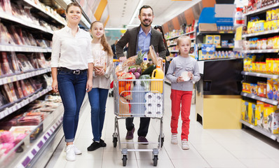 Man with wife and children holding purchases in supermarket