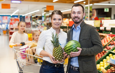 Adult couple with products in fruit department