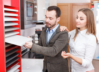 Couple choosing kitchen furniture materials