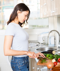 Young girl housewife cutting vegetables at home kitchen