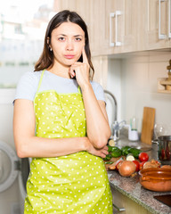 Young  girl housewife in apron looking tired at  kitchen