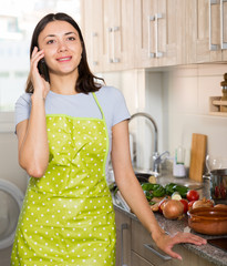 Young girl housewife in apron talking by phone at home kitchen