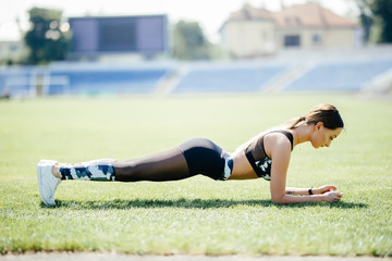 Young happy sportswoman in sportswear making plank exercise on stadium field area outdoors. Healthy lifestyle concept, sport activity.
