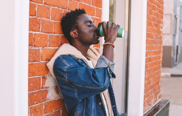 Wall Mural - Break time! Fashion african man drinks coffee on city street, brick wall background