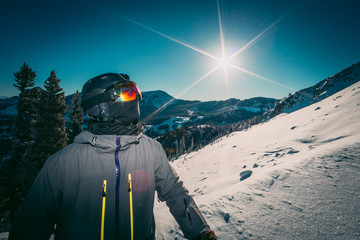 Masked Skier On The Side Of A Resort Mountain On A Bright Sunny Morning