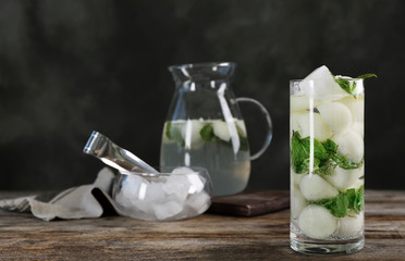 Glass with tasty melon ball drink on wooden table