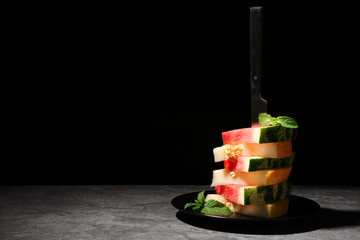 Stacked watermelon and melon slices on plate against black background. Space for text