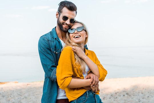 boyfriend hugging laughing girlfriend on beach