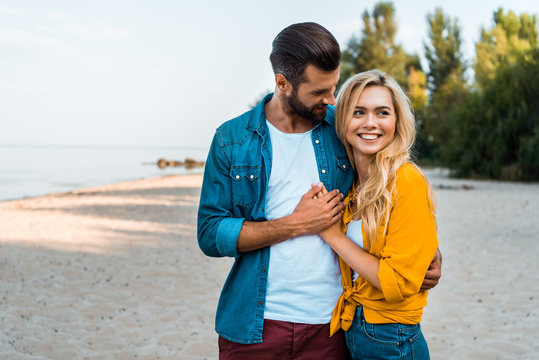 happy young couple hugging and walking on sandy beach