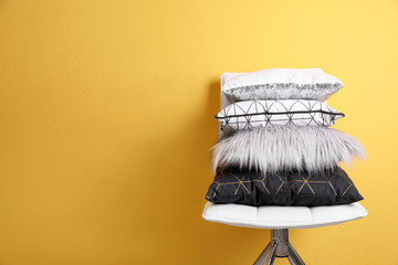 Chair with many different pillows and space for text on color background