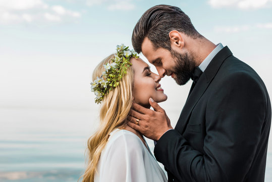 happy wedding couple in suit and white dress touching with noses on beach