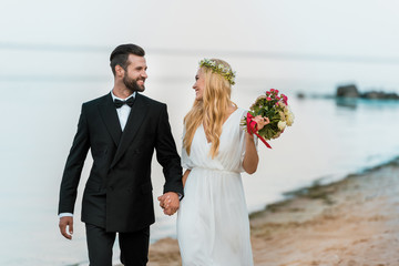 affectionate wedding couple holding hands, walking and looking at each other on beach