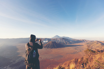 Fotobehang Indonesië successful man hiker taking picture with smartphone at cliff edge on mountain top of volcano bromo Indonesia travel at sunrise time.