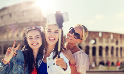 summer vacation, holidays, travel, technology and people concept- group of smiling young women taking picture with smartphone on selfie stick over coliseum in rome background