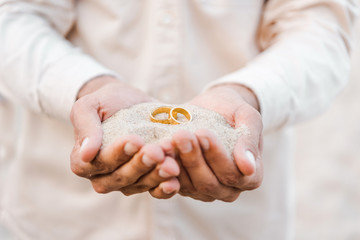 cropped image of groom holding wedding golden rings with sand in hands on beach
