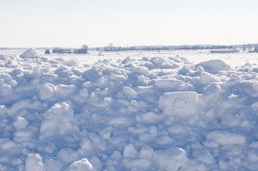Chunks of snow piled high in a rural farm field on a sunny day