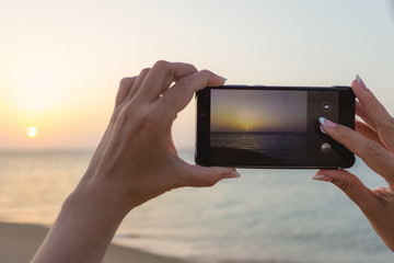Happy european woman taking photo of sunrise or sunset sea using digital camera of smartphone during summer vacation. Closeup color photography of female hands making pictures of landscape.