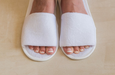 Closeup top view of pair of white new slippers in room of hotel. Woman with beautiful french white and pink fresh pedicure. Horizontal color photography.