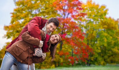 love, relationship and season concept - happy teenage couple hugging over autumn park background