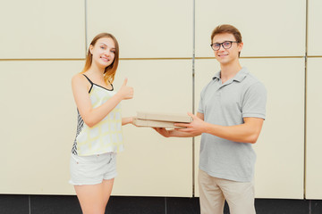 Joyful cute girl showing a thumb up during receiving a pizza from the delivery guy. Outdoors