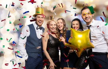 celebration, fun and holidays concept - happy friends with golden party props and confetti laughing