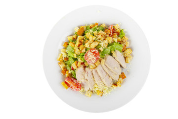 Caesar salad with slices of chicken breast, rusks, cherry tomato, lettuce, cheese on plate, white isolated background, view from above, for the menu, restaurant, bar, cafe