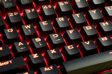 wired mechanical gaming keyboard with  LED illuminated keys; LED light glowing in the background