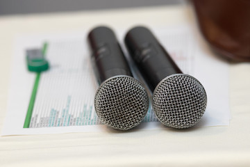 Two black karaoke microphones stand on a white table