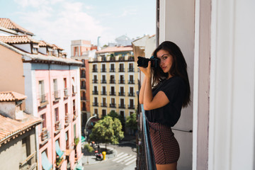 Young woman standing at balcony with photo camera