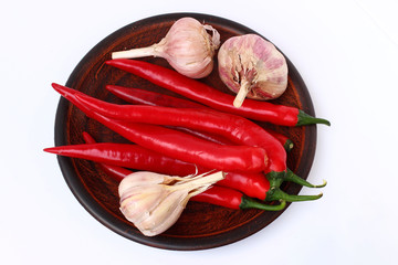 Chili and garlic pepper on a plate on a white background