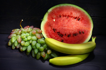 Green grapes, bananas and watermelon on a dark background