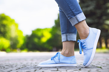 legs of a girl in jeans and blue sneakers on a sidewalk tile, a young woman strolling in a summer park