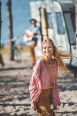 smiling hippie girl dancing while man playing guitar near campervan