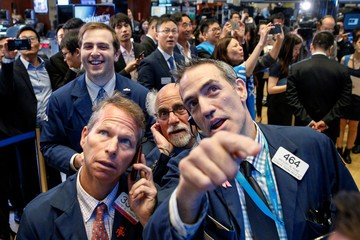 Traders watch the price of X Financial, a Chinese technology personal finance company, following the company's IPO on the floor of the NYSE in New York