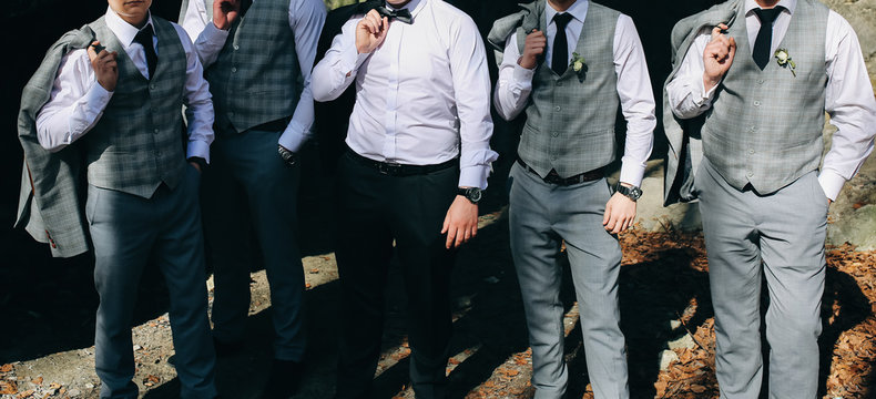 Groom is standing with his friends in the autumn wood. Best man in stylish elegant checkered suits. Groomsmen at wedding photoshoot.