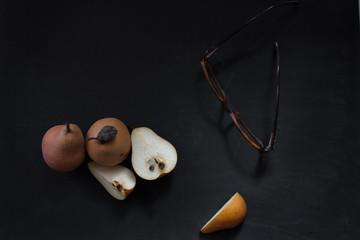 Peras dulces y lentes sobre fondo