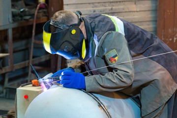 A professional welder in protective thermo-resistant overalls and in a welding mask-chameleon performs welding of the elliptical bottom and the shell of the vessel.